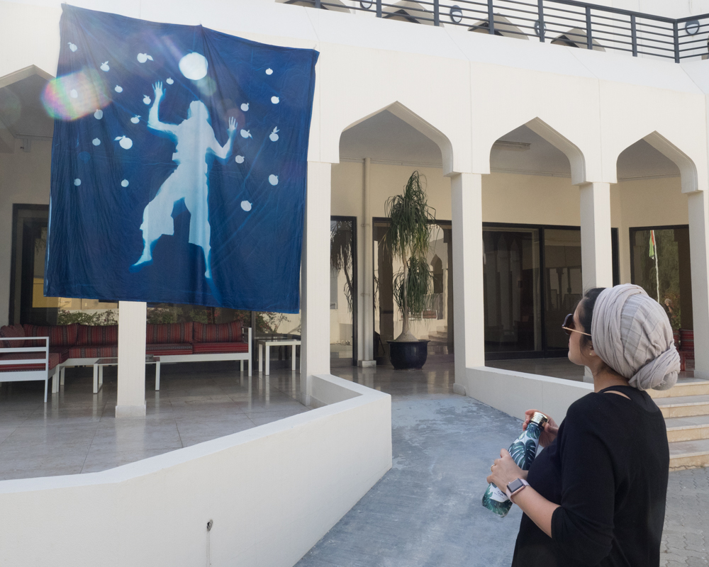 Iranian artist Yosra Emamizadeh views her collaborative portrait at the Tashkeel art studio in Dubai. She is reaching for the moon, and is surrounded by a repeating pattern of pomegranates - a reference to a continuing theme in her own work.